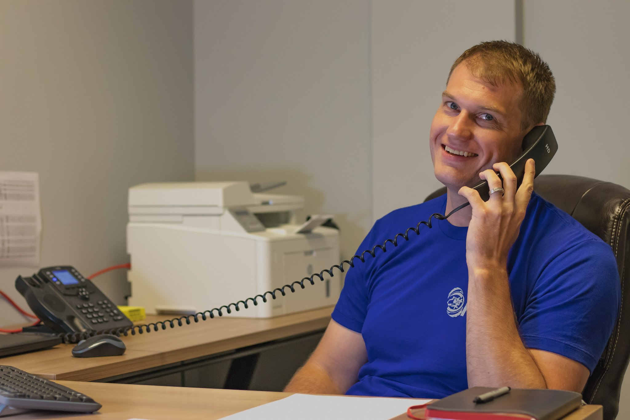 Account Manager, Grant, on the phone smiling